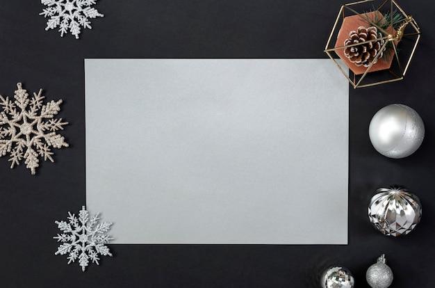 Makiety kartkę z życzeniami na czarno z ozdób choinkowych i konfetti.