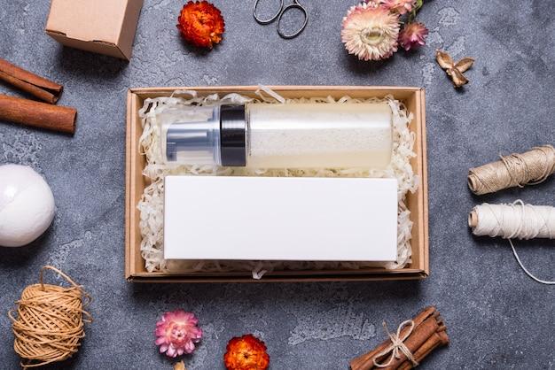 Makiety, kremowa butelka i karton na szarym tle
