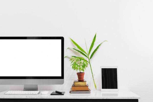 Makiety laptop z dostawami i roślin na stole biurko z marmuru.