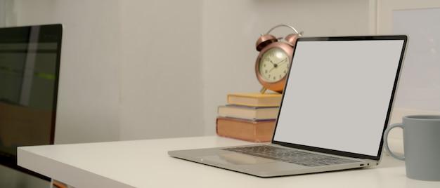 Makiety laptopa na białym stole do nauki z książkami, kubkiem i zegarem w pokoju biurowym