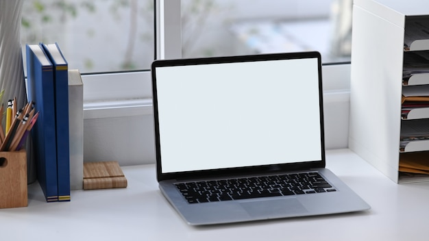 Makiety laptopa z pustym ekranem, książkami i materiałami biurowymi na białym biurku.