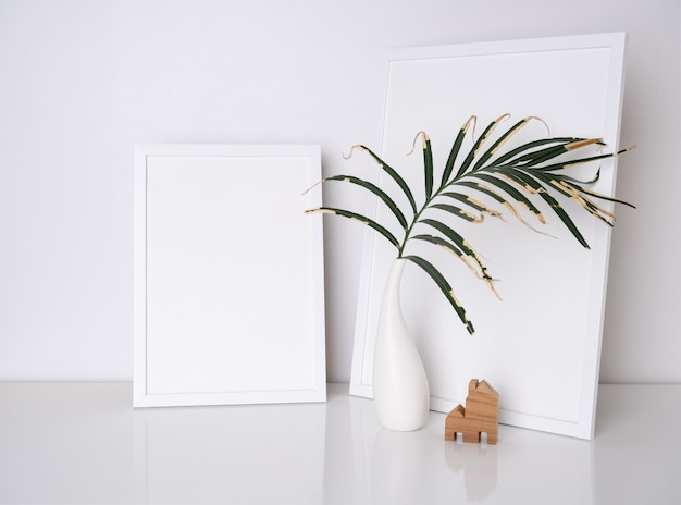 Makiety nowoczesnych białych ramek plakatowych z suchym liściem w białym wazonie na białym stole i cementowej powierzchni ściany