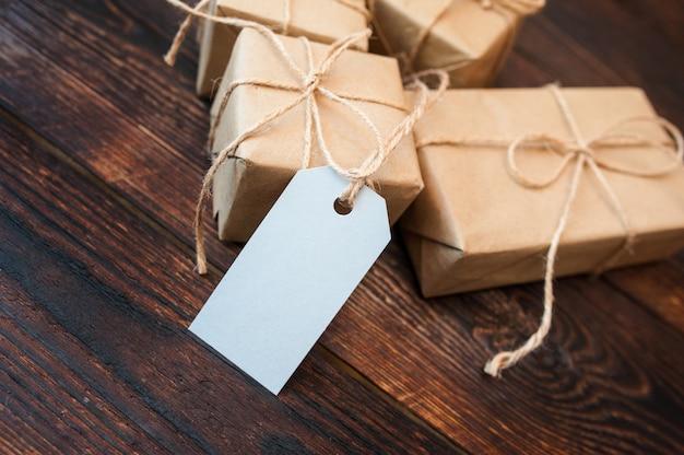 Makiety pudełka na prezenty z papieru pakowego i metki na drewnianej powierzchni