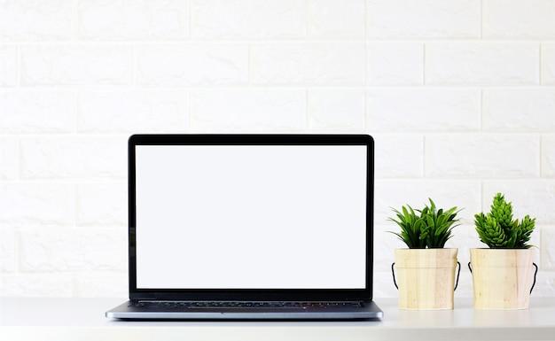 Makiety pusty ekran laptopa z zielonych roślin na białym pokoju ceglanego muru