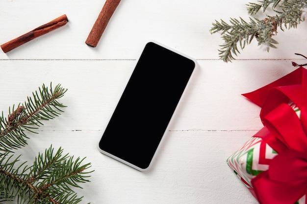 Makiety pusty pusty ekran smartfona na białej drewnianej ścianie z kolorowymi dekoracjami świątecznymi i prezentami.