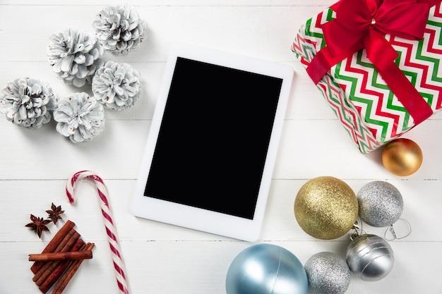 Makiety pusty pusty ekran tabletu na białej drewnianej ścianie z kolorowymi dekoracjami świątecznymi.