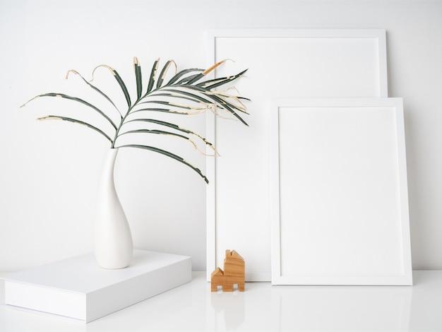 Makiety ramek plakatów suszą liście palmowe w pięknym białym ceramicznym wazonie i model małego drewnianego domu na białej powierzchni biurka