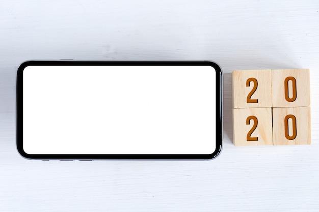 Makiety smartfona i drewniane kostki z numerami symbolizującymi nowy rok