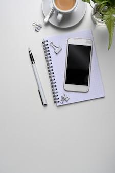 Makiety smartfona, notatnika, filiżanki kawy, roślin i kopiuj miejsce na białym biurku.