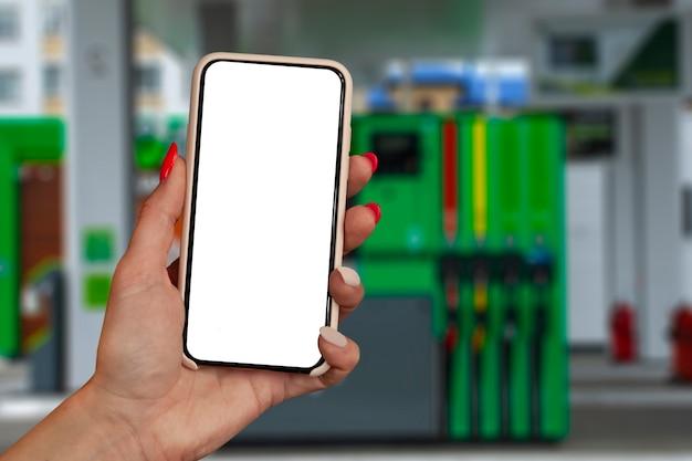 Makiety smartphone w ręku zbliżenie na tle stacji benzynowej. tankowanie płatności online.