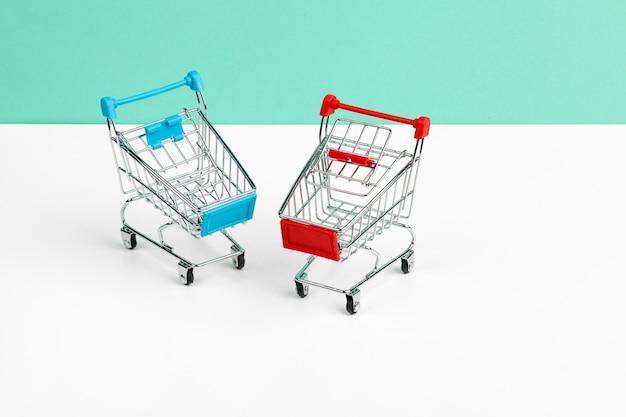 Makiety wózek sklepowy online na biurkowym stole biurowym miękka niebieska ściana