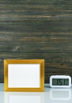 Makiety z pustą złotą ramą i cyfrowym budzikiem na stole z drewnianym tłem