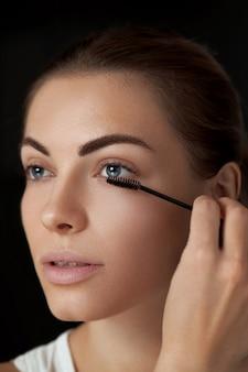 Makijaż brwi. piękna kobieta, kształtująca brwi z zbliżenie pędzla do brwi