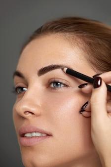 Makijaż brwi. piękny model modelujący brwi z ołówkowym zbliżeniem do brwi. piękna kobieta z profesjonalnym makijażem do konturowania brwi