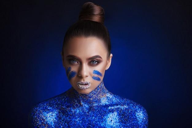 Makijaż i kosmetyki. portret pięknej młodej kobiety z makijażem na błyszczącym ciemnym niebieskim tle. styl imprezowy.