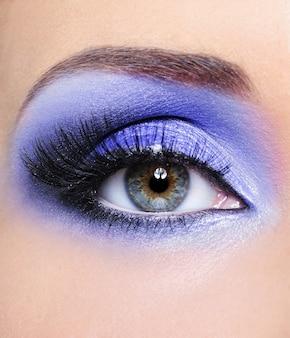 Makijaż kobiecych oczu z jasnoniebieskimi cieniami do powiek