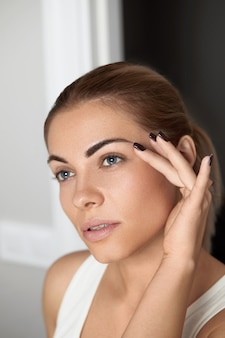 Makijaż kosmetyczny. piękna twarz kobiety z makijażem oczu i brwi oraz długimi czarnymi rzęsami