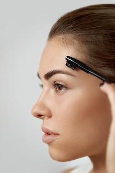 Makijaż kosmetyczny. pielęgnacja brwi. piękna kobieta kształtuje brwi grzebieniem. korygowanie i konturowanie brwi.