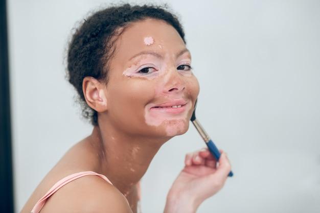 Makijaż. młoda ciemnoskóra kobieta robi makijaż i uśmiecha się