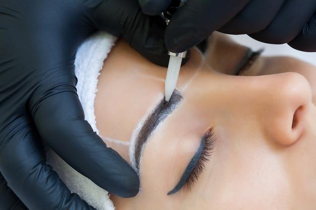 Makijaż permanentny brwi pięknej kobiety o grubych brwiach w gabinecie kosmetycznym