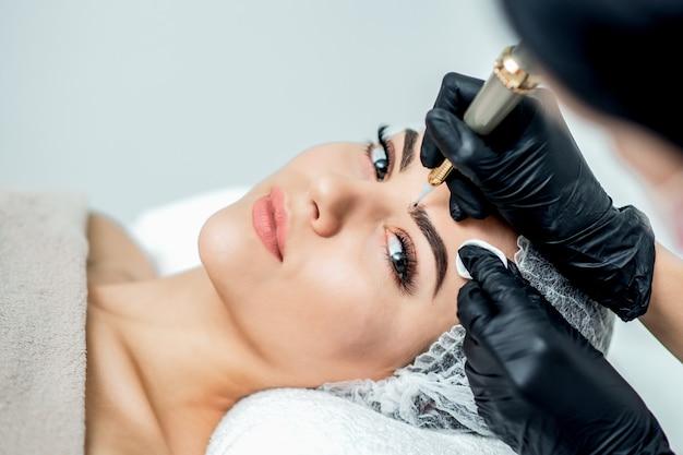 Makijaż permanentny brwi przez profesjonalnego kosmetologa.