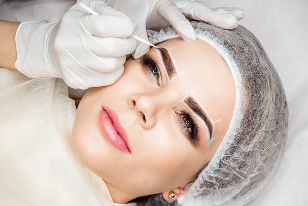 Makijaż permanentny brwi. zbliżenie piękna kobieta z grubymi brwiami w salonie piękności. kosmetyczka robi tatuaże brwi na kobiecej twarzy.