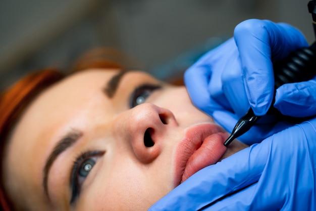 Makijaż permanentny na różowe usta pięknej kobiety w salonie piękności. kosmetyczka robi tatuaże usta. mikropigmentacja. ścieśniać