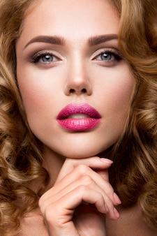 Makijaż. portret glamour modelki pięknej kobiety ze świeżym makijażem i romantyczną falistą fryzurą.