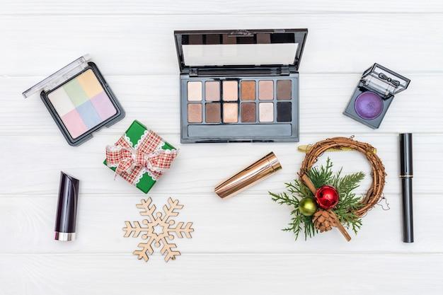 Makijaż prezent, kosmetyki i ozdoby noworoczne i zabawki na białej powierzchni drewnianych