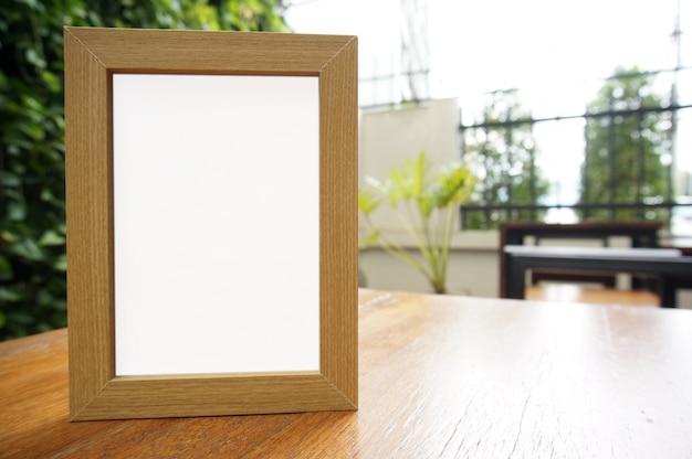 Makijaż pusta biała ramka stojąca na drewnianym stole w kawiarni barowej restauracji. miejsca na tekst. montaż na wyświetlaczu produktu.