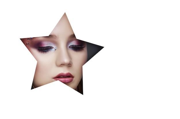 Makijaż twarzy uroda młodej dziewczyny w otworze białej księgi. kobieta z pięknym makijażem, jasne oczy, świetlisty cień w otworze gwiazdy. pielęgnacja skóry, kosmetyki naturalne, kopia przestrzeń, kolorowy cień do powiek