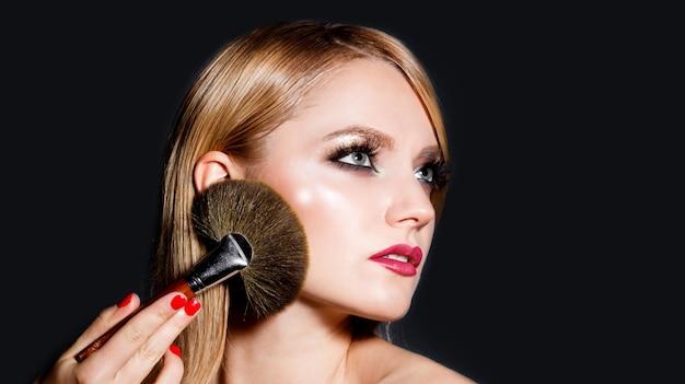 Makijaż w trakcie. portret kobiety na czarnym tle. makijaż moda, kosmetyk. dziewczyna z makijażem, czerwone usta.