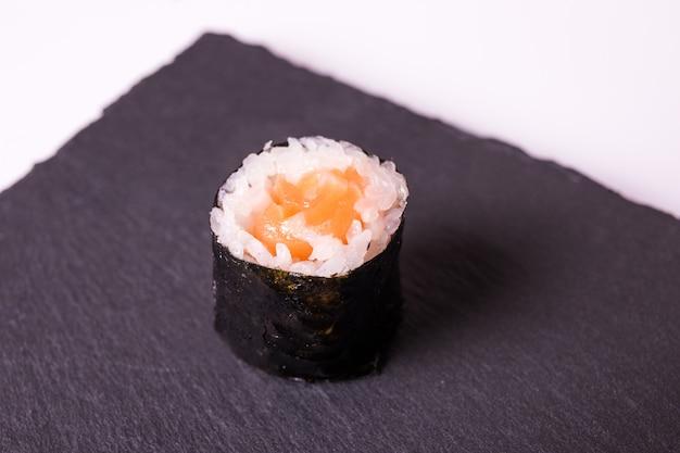 Makisushi roll leży na czarnym talerzu ceramicznym