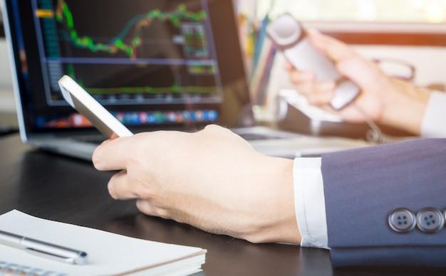 Makler giełdowy obiema rękami w telefonie nawiązującym połączenie z handlowcami