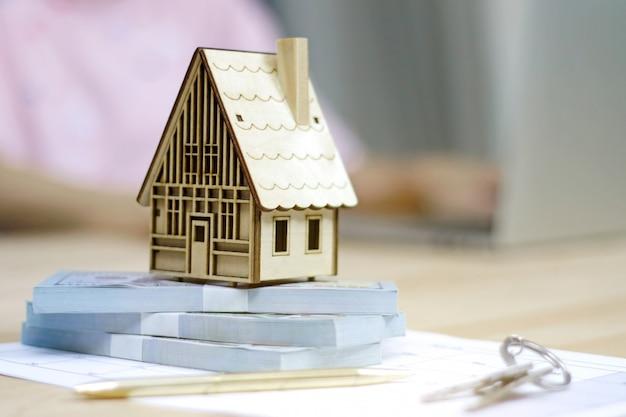 Makler nieruchomości model domu, pieniądze i klucze