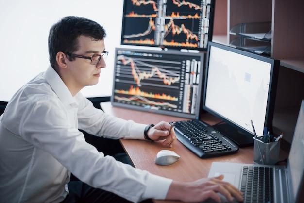 Makler w koszulce pracuje w pomieszczeniu monitoringu z ekranami. giełda obrotu forex finanse graficzny koncepcja. biznesmeni handlujący akcjami online.