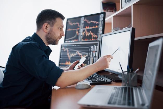 Makler w koszuli pracuje w pokoju monitoringu z wyświetlaczami. giełda handlowa forex finanse grafika. przedsiębiorcy handlujący akcjami online