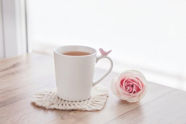 Makrama ręcznie robiona hobby. herbata w filiżance na białej podkładce makramy na drewnianym stole z różą.