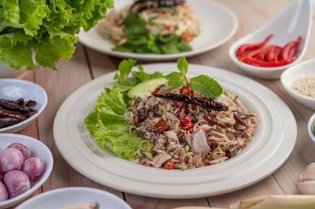 Makrela smażona w głębokim tłuszczu z galangą, pieprzem, miętą, czerwoną cebulą w białym naczyniu.