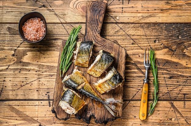 Makrela z grilla na deskę do krojenia. drewniany stół. widok z góry.