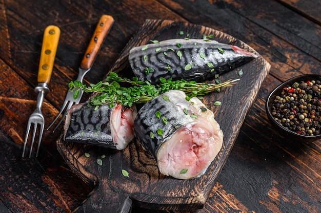 Makrele wędzone kroimy z ziołami. ciemne tło drewniane. widok z góry.