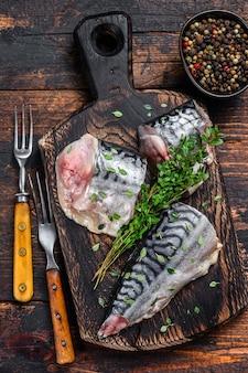 Makrele wędzone kroimy z ziołami. ciemny drewniany stół. widok z góry.