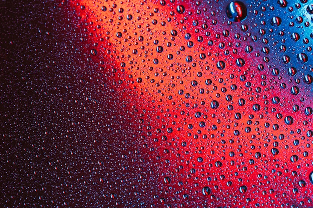 Makro- abstrakcjonistyczne krople woda na jaskrawej powierzchni