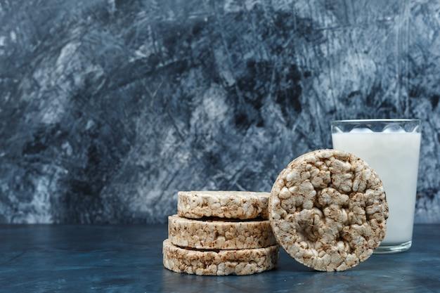 Makro ciastka ryżowe z mlekiem na ciemnym niebieskim tle marmuru. poziomy