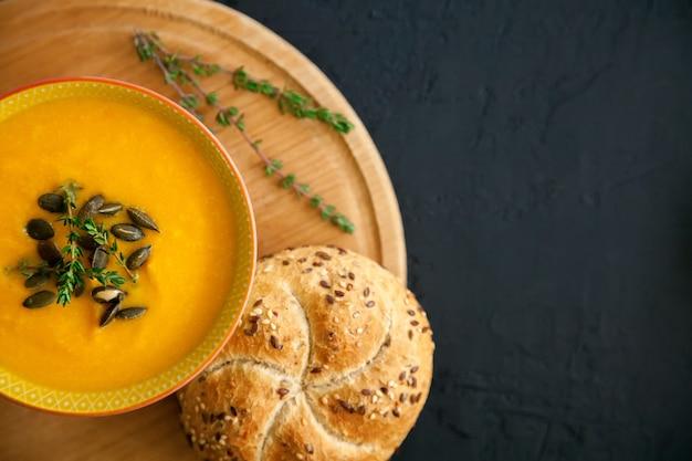 Makro domowej zupy dyniowej z serem, podawana z nasionami, ziołami i bułką, na czarnym tle.