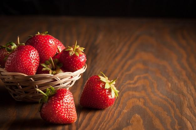 Makro- fotografia świeża dojrzała czerwona truskawka w drewnianym pucharze na nieociosanym tle. organiczne produkty naturalne.
