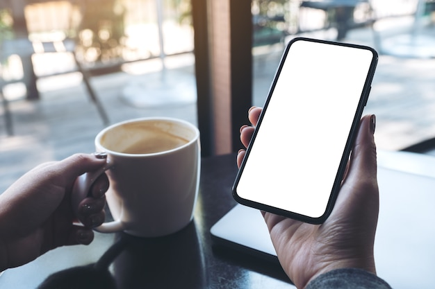 Makro kobiecej ręki trzymającej czarny telefon komórkowy z pustym biały ekran pulpit