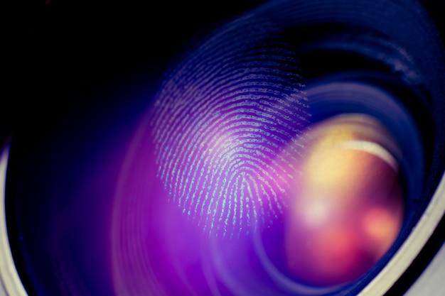 Makro linii papilarnych na obiektywie, czerwone cienie. koncepcja biometryczna i bezpieczeństwa.