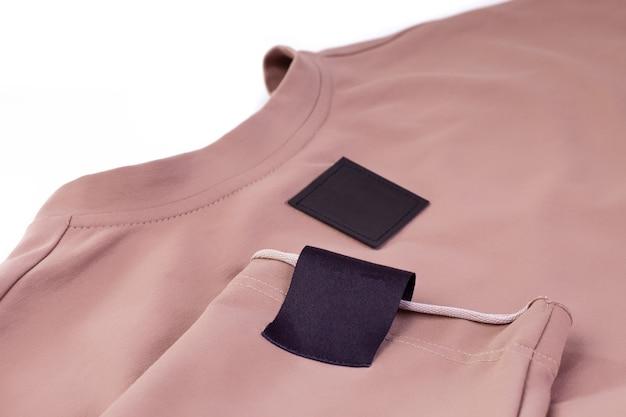 Makro makieta tkaninowa pusta czarna naszywka na logo marki na ramieniu i czarna eko skórzana metka na beżowym swetrze