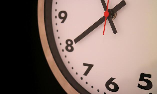 Makro okrągłych zegarów ściennych w kształcie na prawie godzina ósma na czarnym tle
